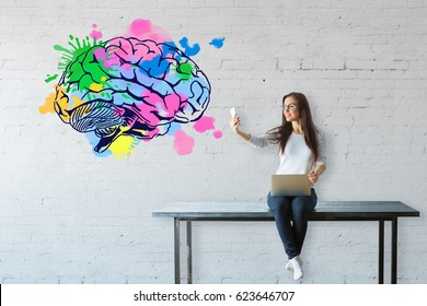 Young woman sitting on table, using laptop and taking selfie with smartphone on white brick background with colorful brain sketch. Brainstorm concept