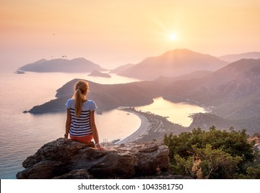 Young woman sitting on the top of rock and looking at the seashore and mountains at colorful sunset in summer. Landscape with girl, sea, mountain ridges and orange sky with sun. Oludeniz, Turkey.