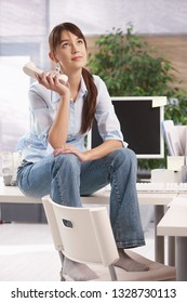 Young woman sitting on top of office desk holding phone receiver and looking lost.