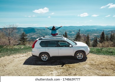 young woman sitting on the top of the suv car at mountain peak enjoying the landscape view