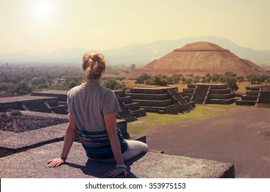 Young woman sitting on the top of pyramid overlooking Teotihuacan at the sunset