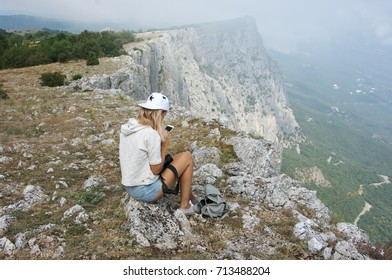 Young woman sitting on top of mountain and looking in smartphone in her hands.