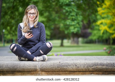 Young woman sitting on the wall in the park, writing a message on her mobile phone, park in the background
