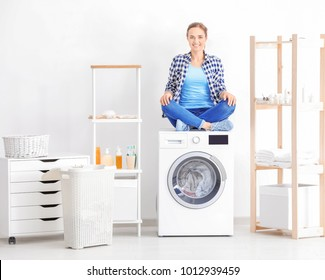 Young woman sitting on washing machine in laundry room