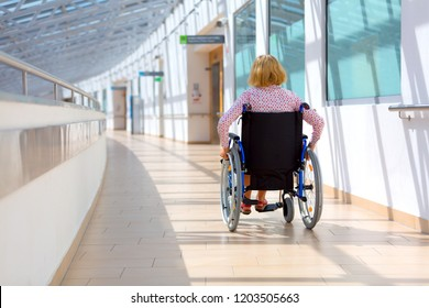 young woman sitting on wheelchair in the medical center, view from back