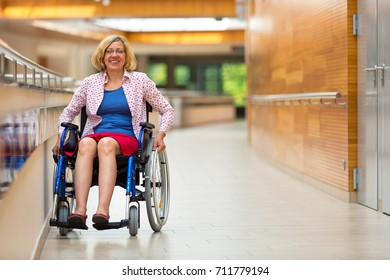 young woman sitting on wheelchair in the medical center and smiling to the camera