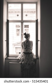Young woman sitting on the window. Vertical, sepia, black and white.
