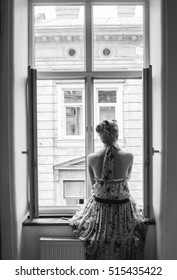 Young woman sitting on the window. Vertical, black and white.