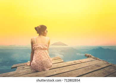 Young woman sitting on wood pier looking mountain landscape view.