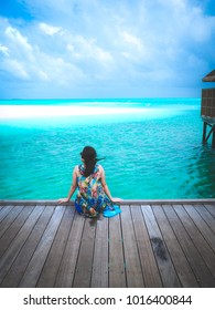 A young woman sitting on the wooden bridge she feel relaxed and enjoy beautiful sea in Maldives
