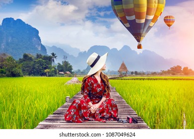 Young woman sitting on wooden path and look at balloons with green rice field in Vang Vieng, Laos.
