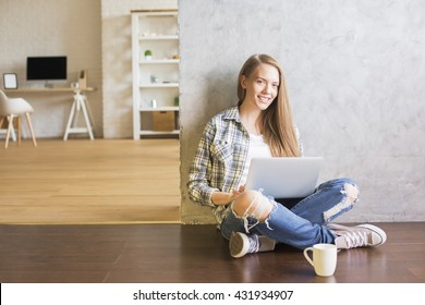 Young woman sitting on wooden floor with coffee in interior and using laptop