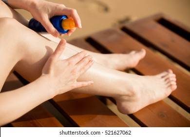 Young woman sitting on wooden sun lounger on sunny southern sand beach, holding bottle of sunscreen lotion, applying sunblock cream on legs, close up. Sunburn and cancer protection concept