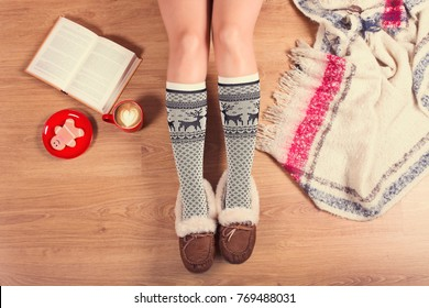 57f5f276aa44 Young woman sitting on the wooden floor with cup of coffee
