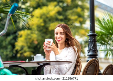 Young woman sitting in the open air cafe with cup of coffee and bicycle on background in the city centre