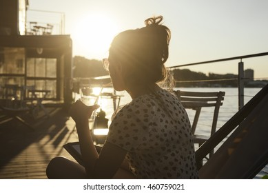 Young woman sitting in outdoor cafe, drinking cocktail and watching the river at sunset. Summer holiday chilling out. Retro style image.