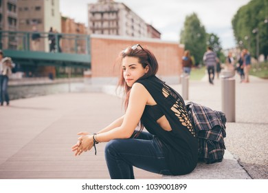 young woman sitting outdoor looking away - pensive, worried, technology concept