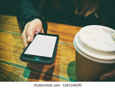 The young woman sitting outside the cafe and texting the message in her smartphone while drinking coffee