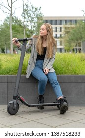 Young woman sitting in a park with e scooter