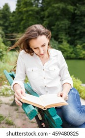 Young woman sitting in park near pond and reading book. Pretty caucasian girl with book relax on the bench