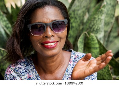 young woman sitting in a park in sunglasses watching the camera smiling.