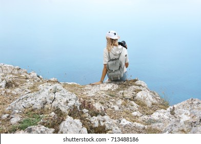 Young woman sitting and photographing on top of mountain against sea at cloudy weather. Back view.