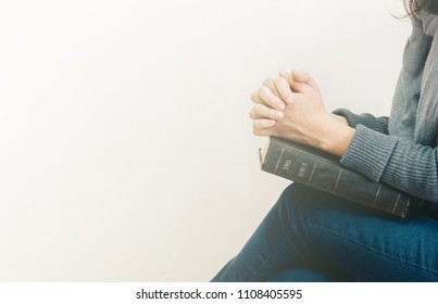 Young woman sitting and prayer on bible.copy space