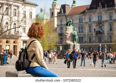 Young woman is sitting in the Presern square and admiring Presern monument in Ljubljana, Slovenia