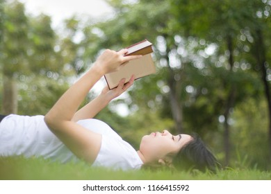 Young woman sitting and reading her favorite book on a  green meadow covered in a nice sunny summer/spring day.Concept of recreation, education and study , curiosity, leisure time