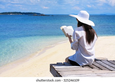 Young woman sitting and reading over the beautiful beach