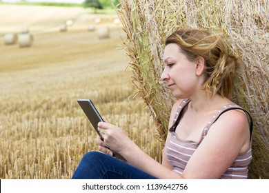 Young woman sitting relaxed with a tablet on a field