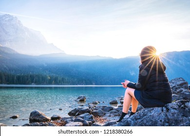 Young woman sitting relaxing on the rock with mountain and lake background at Eibsee lake Germany.Happy Vacation holiday in beautiful outdoor scene landscape and sunset Travel Journey Freedom concept.