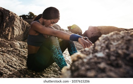 Young woman sitting rocks outdoors after her workout and looking down. Female athlete taking rest after fitness training.