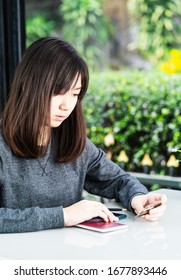 Young woman sitting sholding credit card and passport on deck in home office