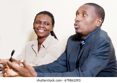 Young woman sitting side by side with her partner, looks at him and laughs.