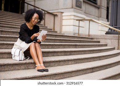 young woman sitting in the street using a tablet