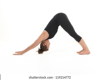 young woman sitting in stretching yoga pose, dressed in black, on white background
