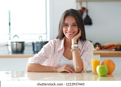 Young woman sitting a table in the kitchen. Young woman