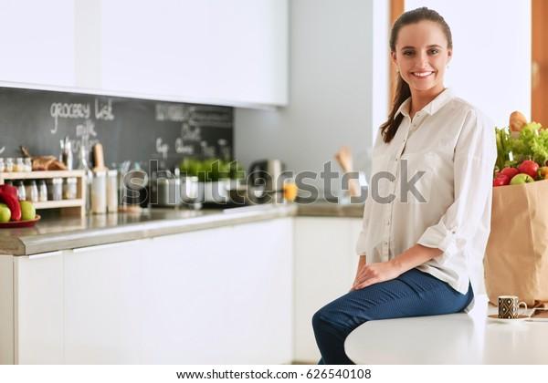 台所のテーブルに座っている若い女性。