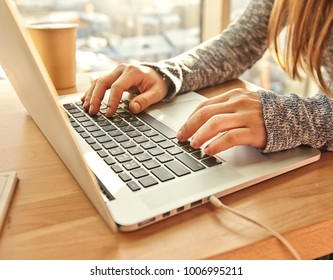 The young woman is sitting at the table and working with her modern laptop