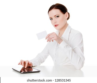 Young woman sitting with a tablet computer and holding a credit card.