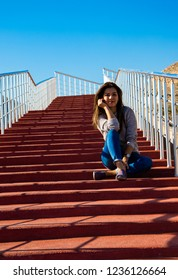 a young woman sitting and thinking on the red stairs