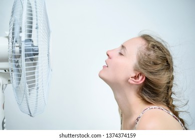 Young woman sitting under a fan with closed eyes from pleasure. Summer heat. White background