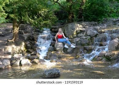 young woman sitting at waterfall