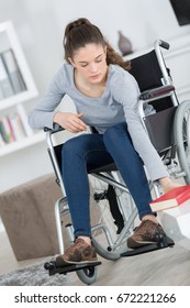 young woman sitting in wheelchair reaching a book