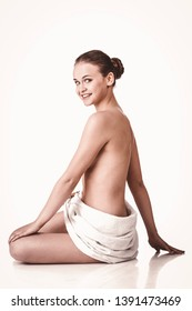young woman sitting wrapped in towel on white background. Spa concept.