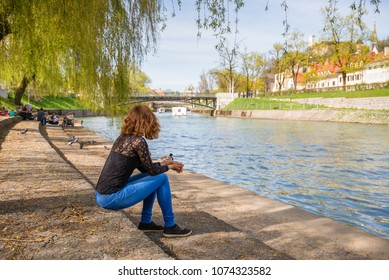 "Young woman is sittng on the banks of Ljubljanica river at Trnovo ""beach"" admiring the beautiful Ljubljana old town in Ljubljana, Slovenia."