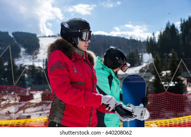 Young woman in ski suit, with helmet and ski goggles putting on gloves while standing near the fence in a ski-resort in winter period