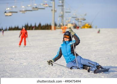 Young woman skier in blue ski suit trying get up after the fall on mountain slope. Ski resort. Winter sports concept. Ski resort at Carpathian Mountains