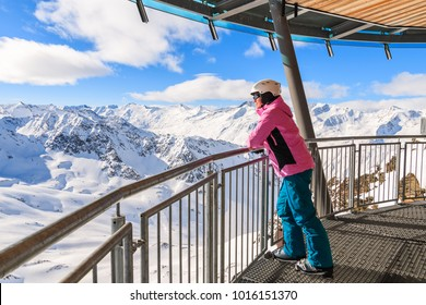 Young woman skier looking at mountains from restaurant terrace in Hochgurgl-Obergurgl ski area, Tirol, Austria